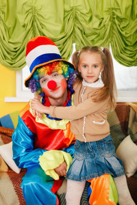 Little girl hugging a cheerful clown.